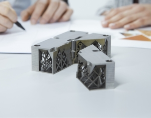 3D-Objekt aus Metall vor Arbeitsskizzen